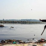 New Delhi: India: 2014  Sahil's throws small stones to move the elephants deeper into the water. Although polluted, the Yamuna is an every day routine for the elephants
