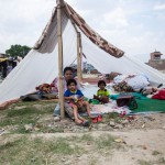 Paris Dada: Kathmandu: 13MAY2015  A family shelter from the midday sun in their newly constructed tent. No one knows how long they should stay or when it will be safe