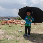 Paris Dada: Kathmandu: 13MAY2015  Four years old Ankit Somai shelters under an umbrella from the hot midday sun.