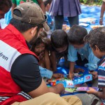 Sindhupawlchok: Nepal: 20MAY2015  Children at a Temporary Learning Centre established by Save the Children practice reading with flash cards with Save the Children staff member Dave Hartman.